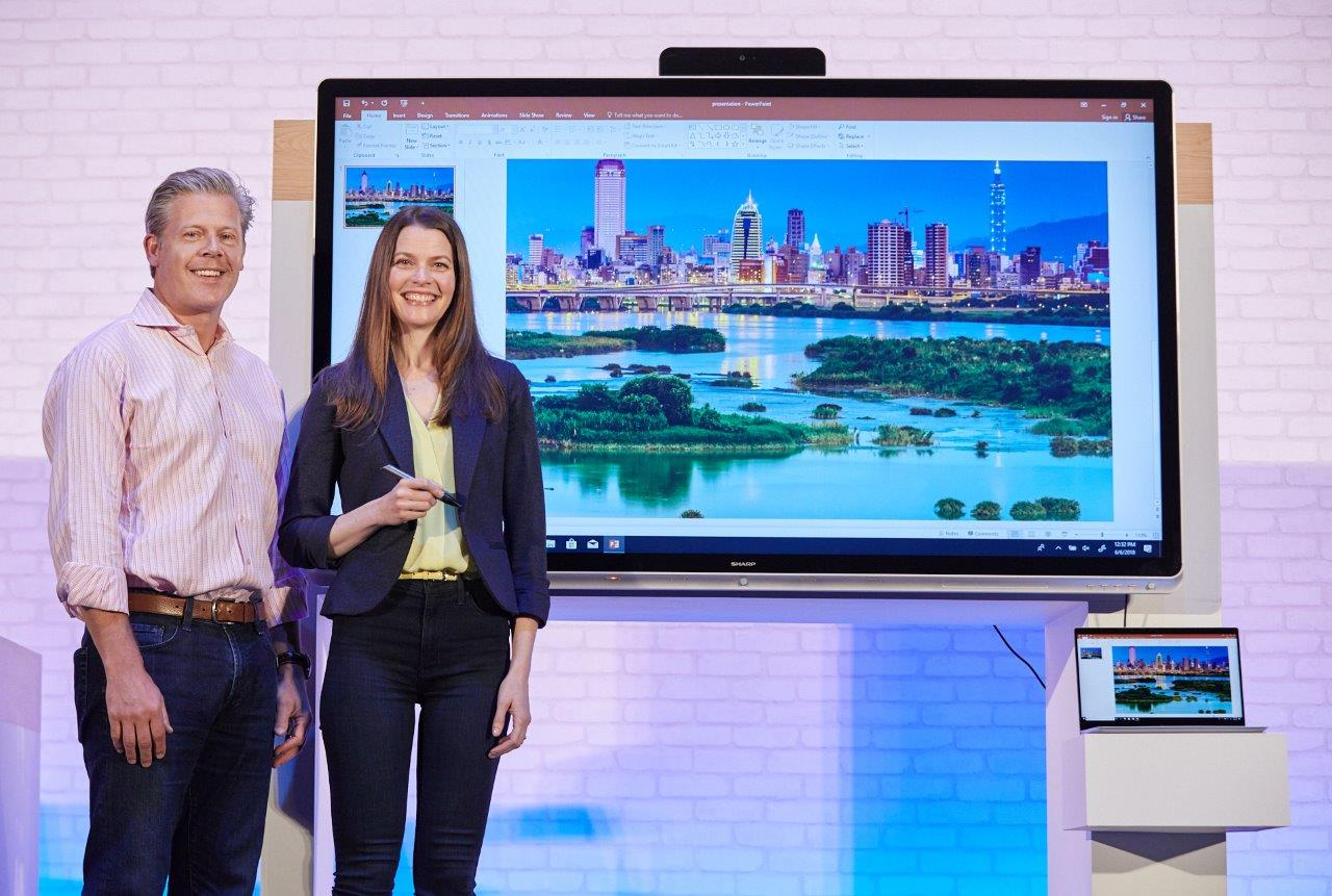 """Nick Parker and Roanne Sones stand on stage with the 70"""" Windows Collaboration Display from Sharp"""