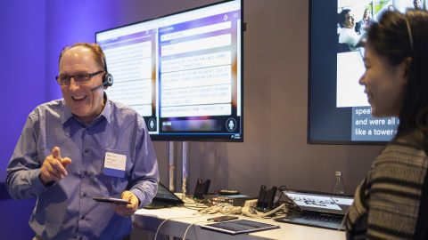 Will Lewis and Amanda Song face each other in front of dual monitors showing real-time translation as the speak